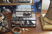 Small glass jewelry box atop wooden table.
