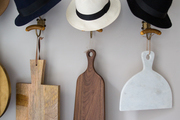 Hats and cutting boards hanging from from vintage hardware.