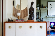 A white cabinet with sculptural decor.