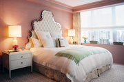 Grass-cloth wallpaper and a white tufted headboard in a master bedroom