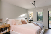 A bedroom with blush bedding and a cozy knit throw on it.