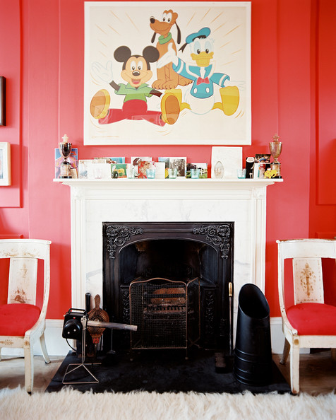 Mantel - Disney-themed art above a mantel in a red-walled living space