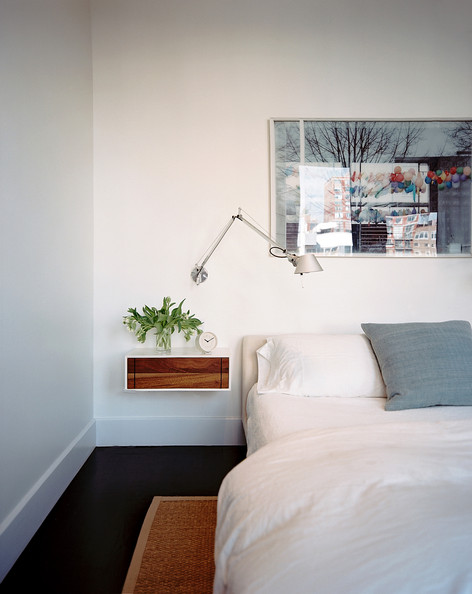 Modern Bedroom - White bedding and a swing-arm sconce above a bedside table
