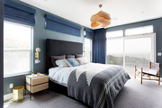 A contemporary bedroom with beachy vibes and blue walls.