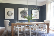 Large scale art hanging behind white and brown dining room table.