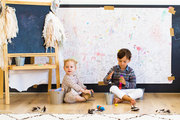 Kids on a playroom's hardwood floor near a rug, an artwork-in-progress on a chalkboard behind them