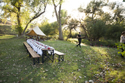 A view of a long dining table outdoors.