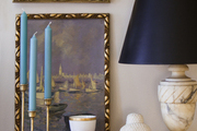 Candlesticks, framed art, and books on a tabletop
