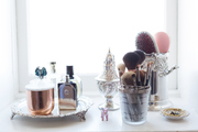 A detail of makeup brushes and perfume on a table.