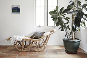A serene space with white walls and a rattan lounge chair.