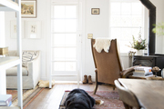 A dog lays on a vintage rug in this farmhouse living room.