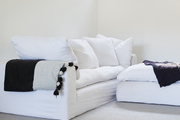 This is a white sofa and ottoman topped with throw blankets.