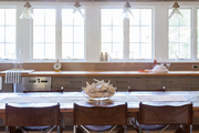 Four pendant lights above a dining table in a kitchen