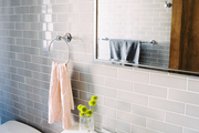 Gray subway tile and a striped hand towel in a bathroom