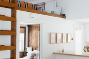 """Inside the cottage, Stier's mezzanine level allows her to host friends and family, who come to visit. The otherwise stark, snowy space, provides a pop of color overhead, thanks to a bold '70s throw. """"I love the tall ceiling in the living room and the loft, it gives the space such a unique feel and makes my home feel larger than it is,"""" she says."""