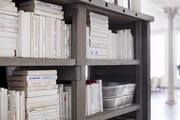 White books and other items stacked in wood shelf.