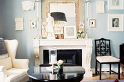 A white wingback chair beside a mantel styled with art, candlesticks, and an antique mirror