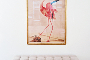 A portrait of a pink flamingo hung above a tufted bench