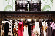Palm-frond wallpaper above a rack of kate spade new york clothing