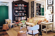 A living space with a mirrored coffee table, a green folding screen, and striped hardwood floors