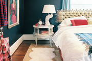 A vintage tufted headboard and layered rugs in a bedroom with dark walls