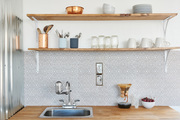 A detail of a kitchen sink with a tile backsplash and wooden shelves.