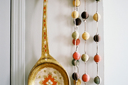 A string of beads and a large ladle hung from a wooden coat rack