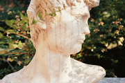 An antique bust surrounded by mature landscaping