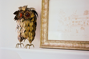 A vintage Curtis Jere-style owl watches over a country mantel.