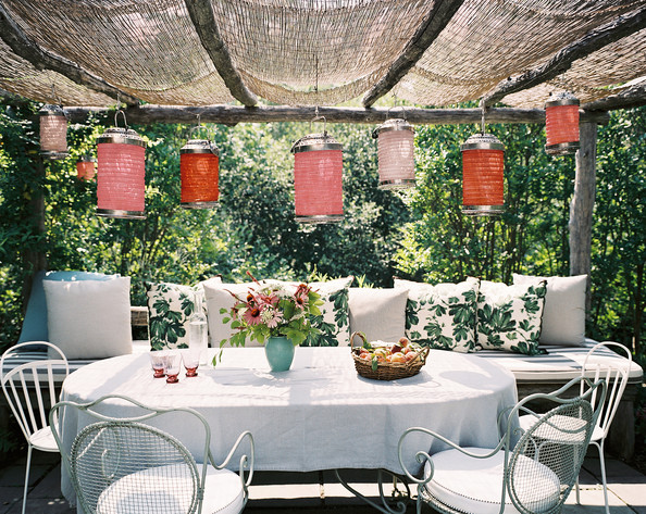 Patio - Paper lanterns suspended above a bench of pillows and an oval dining table
