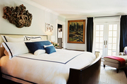 French doors and a wooden bed with white-and-blue bedding