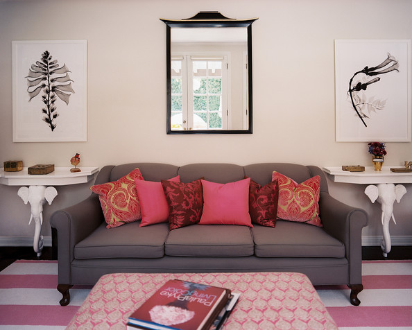 pink a gray couch with pink pillows atop a striped rug