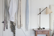Hanging textiles next to vintage light atop nightstand in white walled room.