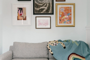 A gallery wall hangs above a gray love seat.