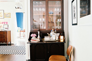 A wooden secretary desk with a tray of bar essentials