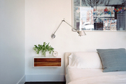 White bedding and a swing-arm sconce above a bedside table