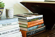 Stacks of books, a candle, and a plant atop a wood table