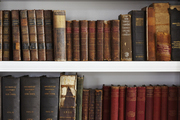 Detail of a bookshelf filled with antique books.