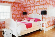 Pink-and-orange wallpaper and a zebra-print rug in a bedroom