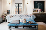 A tufted couch arranged with a factory-cart coffee table