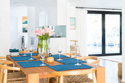 Natural wooden dining table with blue placemats and wishbone chairs.
