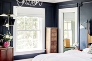 A French-style bedroom with deep blue walls.