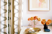 Patterned curtains next to a white dresser topped with vases of orange flowers