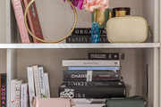 A bookshelf stored with purses, books, and boxes.