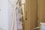 A brown room divider and items hanging on a white wooden rack.