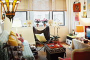 A butterfly chair and a red armchair on either side of a zebra-print storage ottoman
