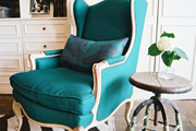 A green armchair beside a wooden stool used as an end table