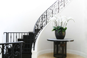 A gorgeous white staircase with rod iron railing.