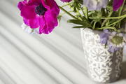 Purple flowers arranged in a detailed gray vase