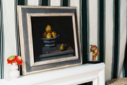 A white mantel topped with art and flowers against walls draped with striped fabric
